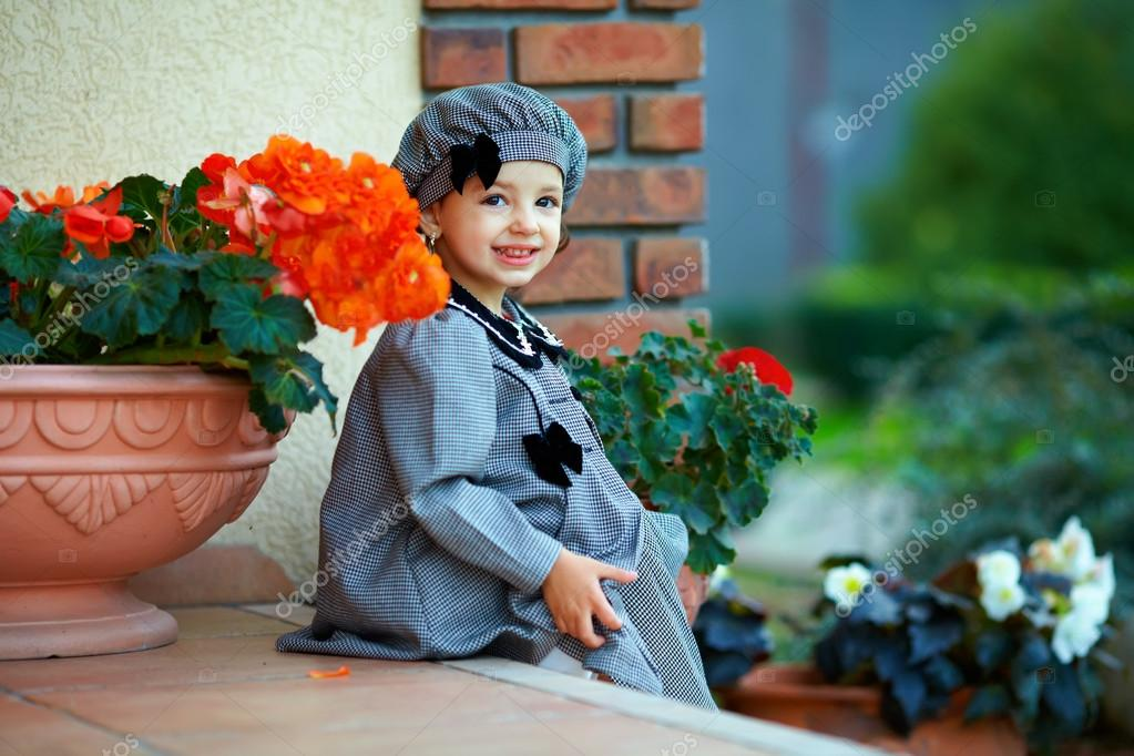 Cute little baby girl sitting on house porch steps