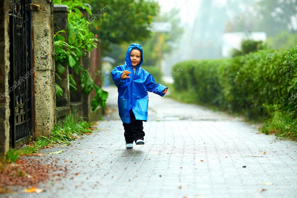 Happy baby boy running the street under the rain
