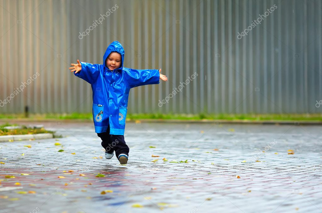 Happy baby boy running the street, rainy weather