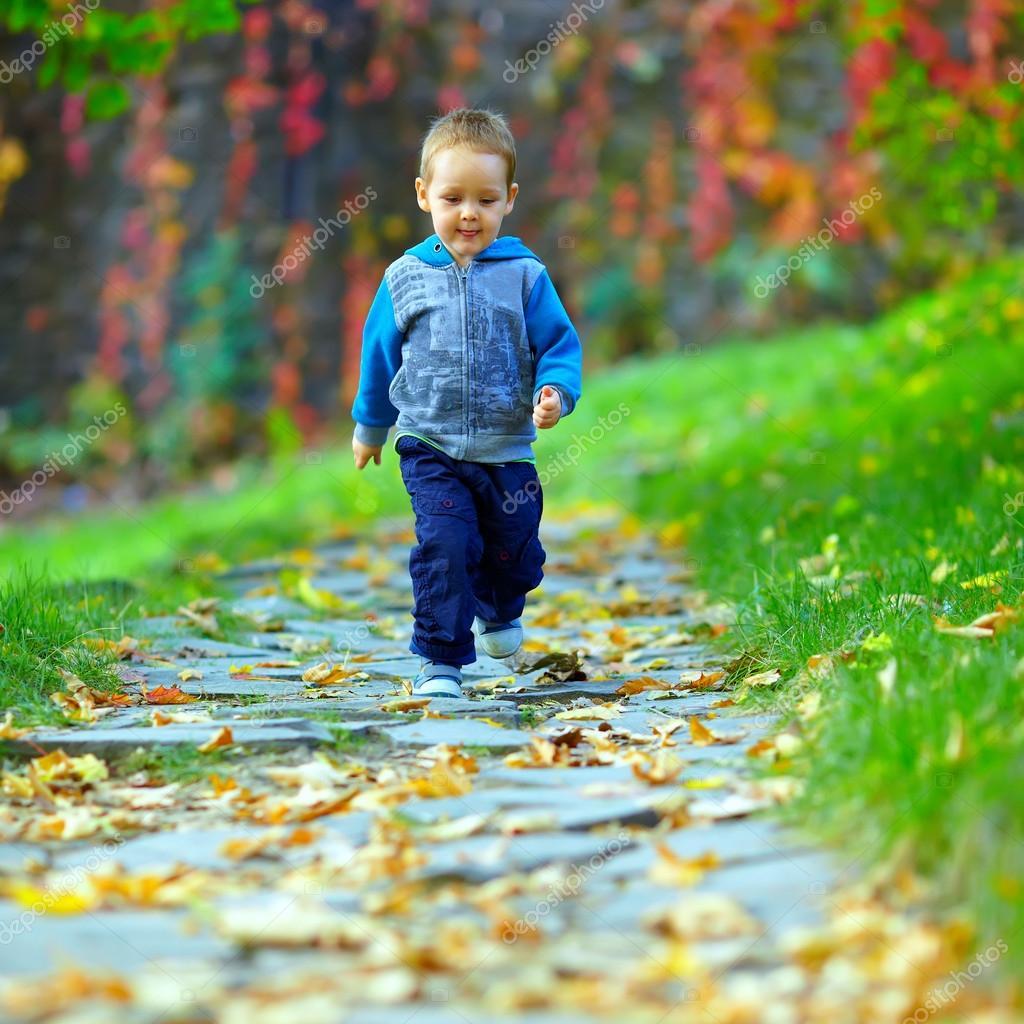 Cute baby boy running beautiful autumn footpath