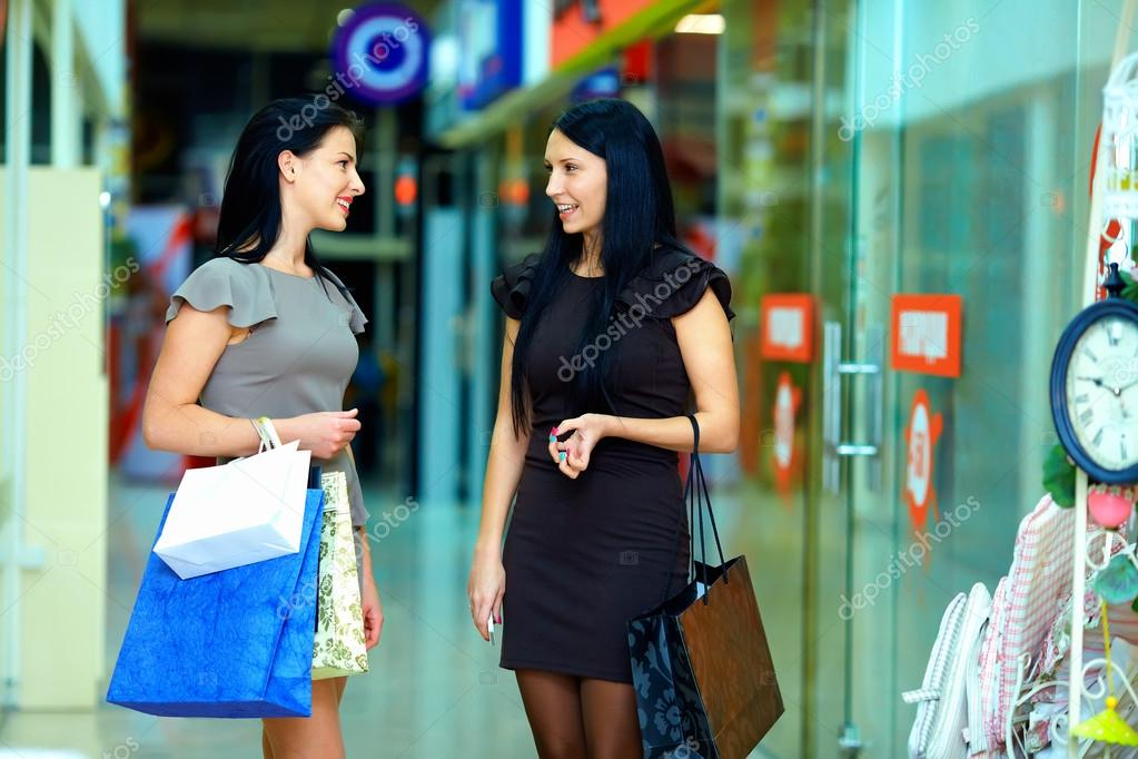 Smiling female friends shopping in the city mall