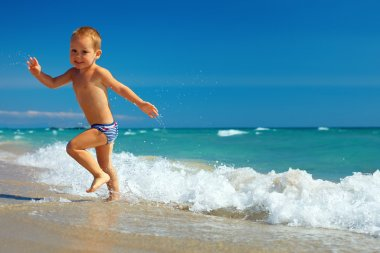 Happy baby running from surf on the beach