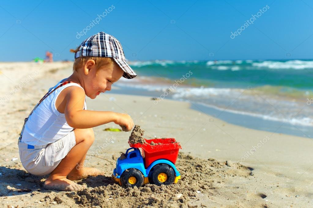 cute happy kid playing with toy on beach