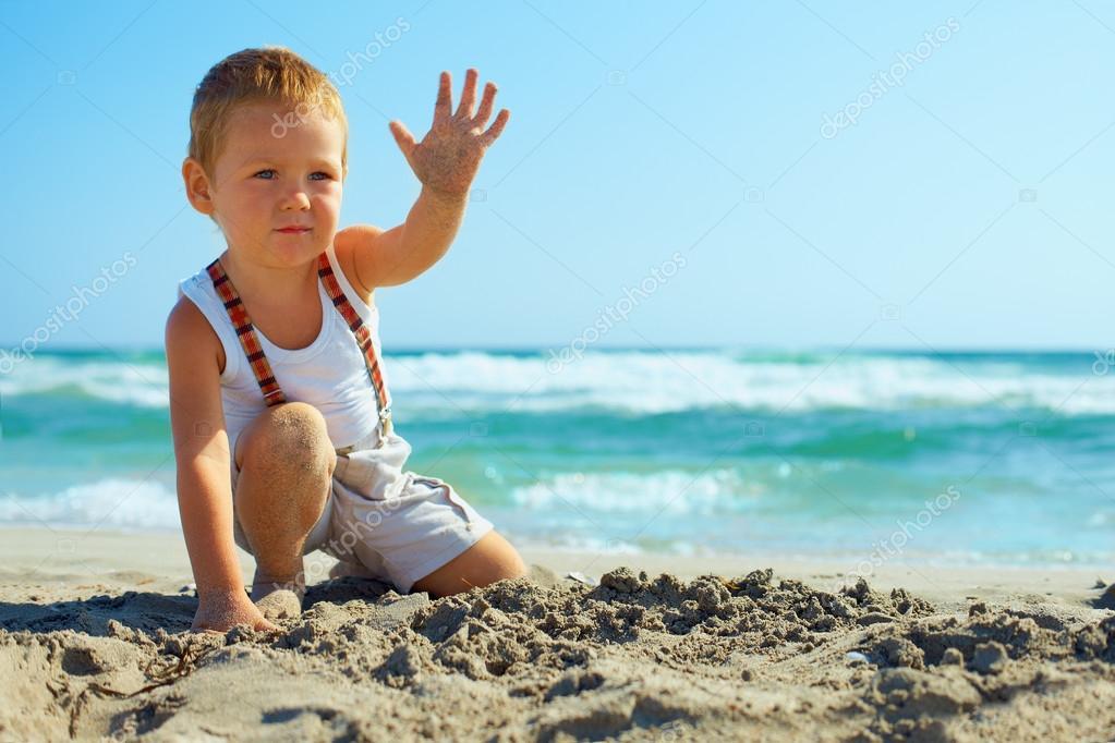 stylish baby boy waving hand on the beach