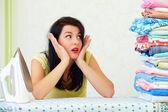 Fotografie unavená hospodyňka s obrovskou hromadu vyžehlené prádlo