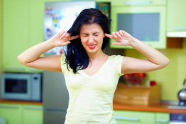 angry woman closes ears with fingers, home interior