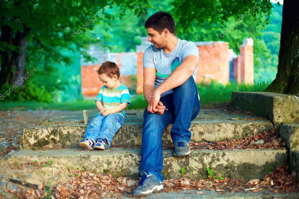 father and son talk, while sitting on old stairs among trees