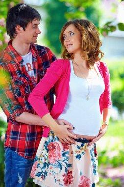 sensual pregnant couple in blooming spring garden