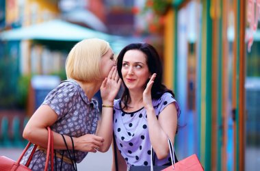 tricky young women gossip on the city street