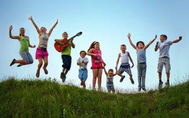 happy kids jumping on summer field