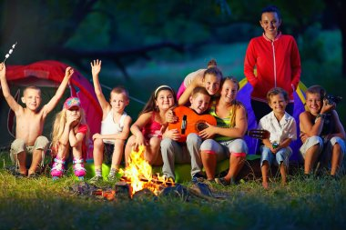 happy kids having fun around camp fire