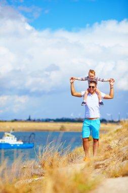 happy father and son enjoying seaside landscape