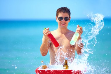 happy man with drinks and water splash on the beach party