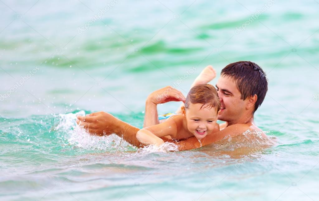 happy father and son swimming in sea water