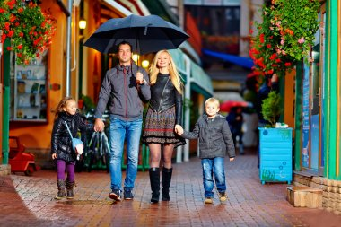 Happy family walking under the rain on cozy colorful street