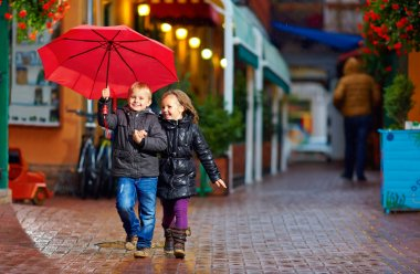 happy kids running the street under the rain
