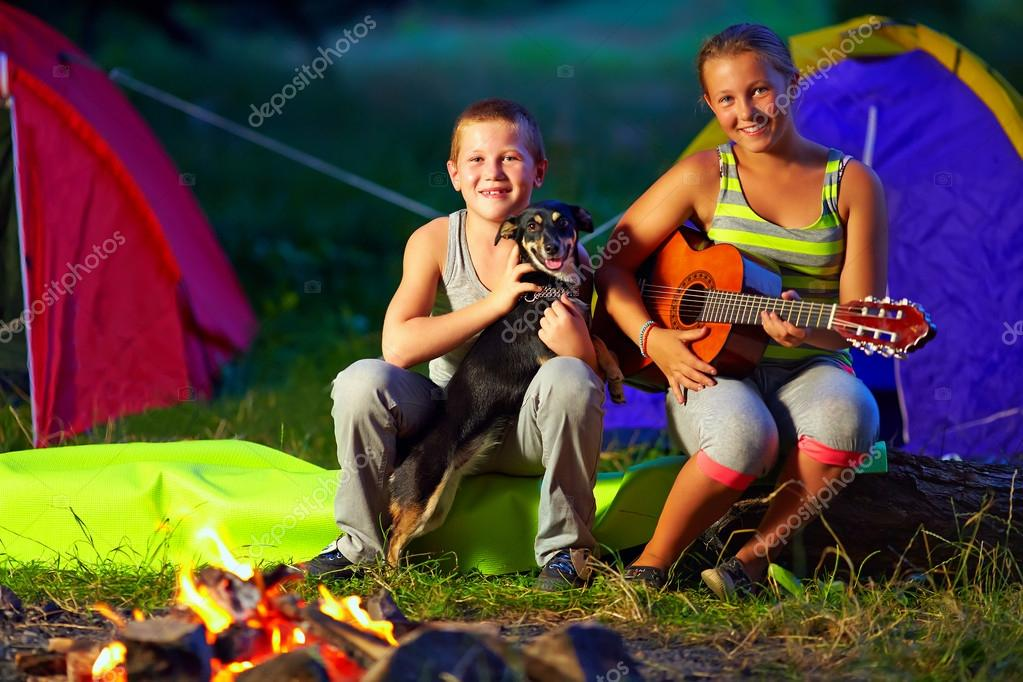 Happy teenagers singing songs around camp fire