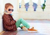 aranyos divatos fiú bőr kabát és gumi cipő