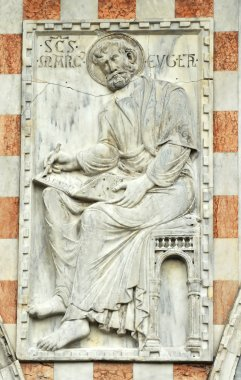 Life size marble relief panel of saint mark the evangelist writing his gospel, on the wall of st mark's basilica, Venice. stock vector