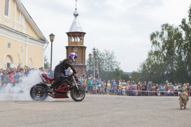 Motorcycle Show on Cathedral Square in village Verkhovazhye, Vologda Region, Russia. Alexei Kalinin burneth his motorcycle tires