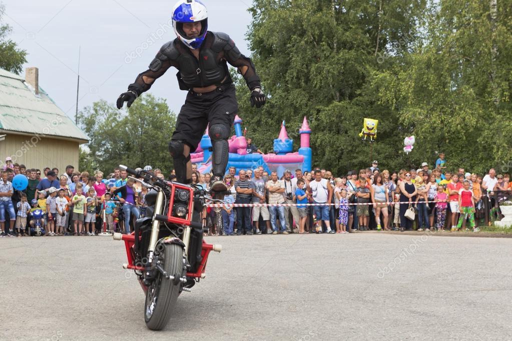 Alexei Kalinin rides standing on a motorbike  Moto show in Verkhovazhye, Vologda region, Russia