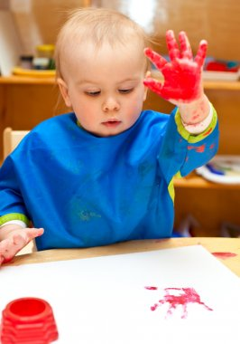 Child painting with hand