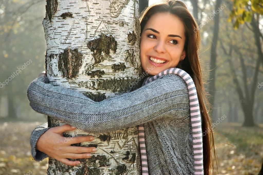 Woman smiling and hugging a birch tree