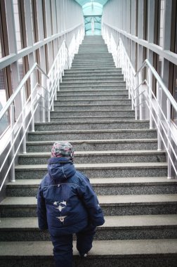 boy makes the first steps up stairs