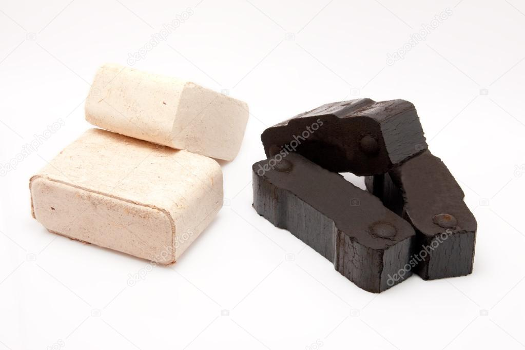 Coal briquettes and pieces of wooden fire briquettes isolated on white background