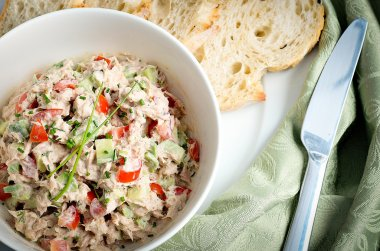Tuna and avocado salad served in a bowl with ciabatta toasts