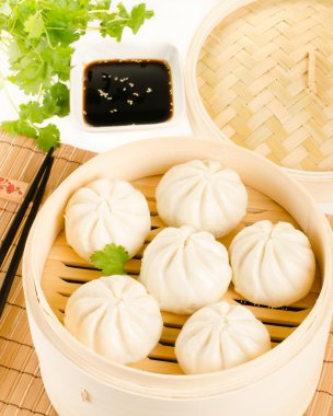Chinese steamed buns in bamboo steamer basket with cilantro, soy