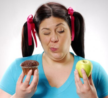 Fat girl holding a chocolate snack cake and apple,happy girl holding a chocolate snack cake and apple,
