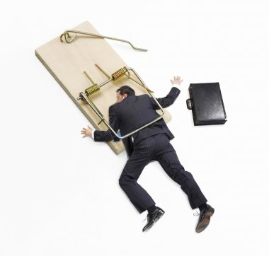 Businessman trapped on mousetrap on white background