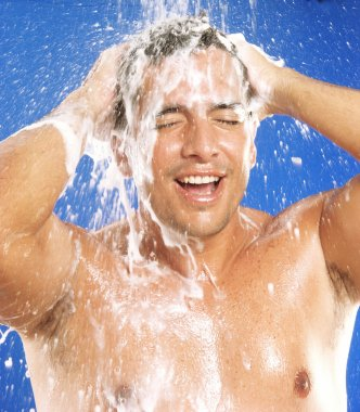 Young latin man taking a shower.