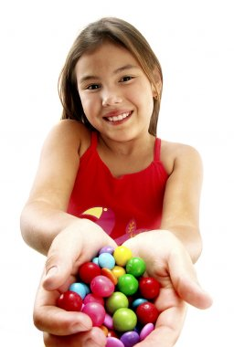 Young girl holding candies.