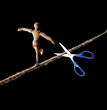 Scissors cutting the rope to a tightrope walker