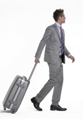 Young businessman walking and pulling his luggage.