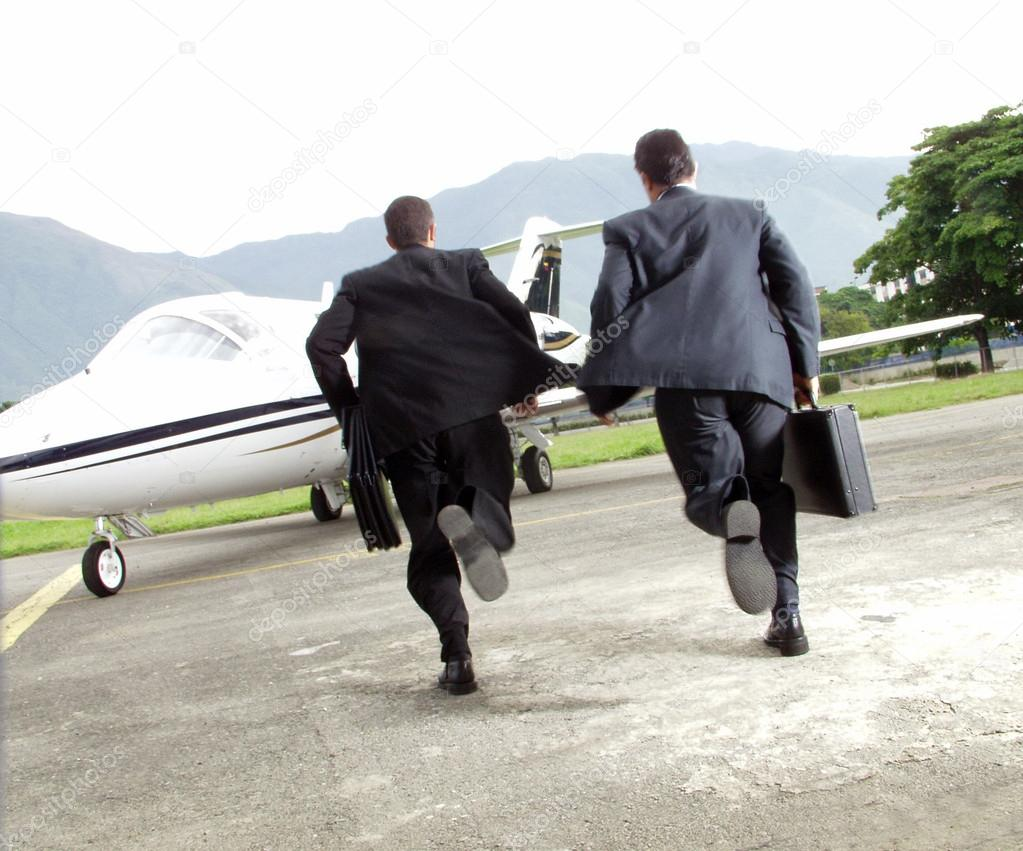 Two businessman running towards a plane