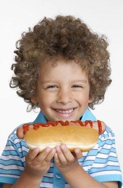 Little kid eating hot dog,Kid holding hot dog.