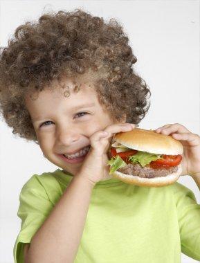 Little kid holding a big hamburger,eating hamburger.