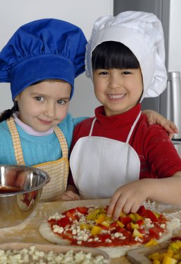 Two Little girls cooking a pizza in a kitchen.Little kid in a kitchen together.