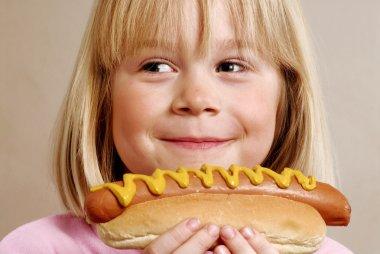 Little girl eating a hot dog