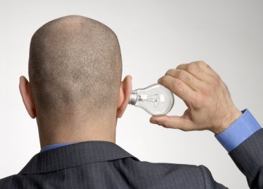 Rear view from a bald head man holding a bulb lamp on his ear.