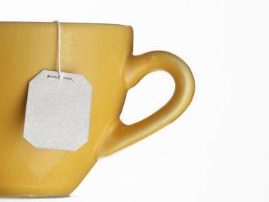 Hot tea bag on yellow cup.