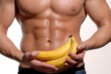 Shaped and healthy body man holding a fresh bananas