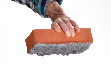 Constructor worker holding a cement construction brick.