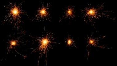 Set of burning sparklers on black background.