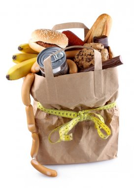 Paper shopping bag with high-calorie foods and measuring tape