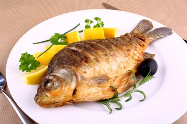 Fried carp on white plate with knife and fork