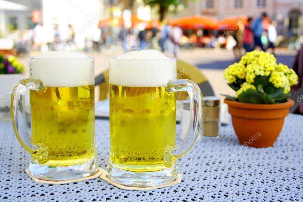Two steins beer garden in the city, soft focus